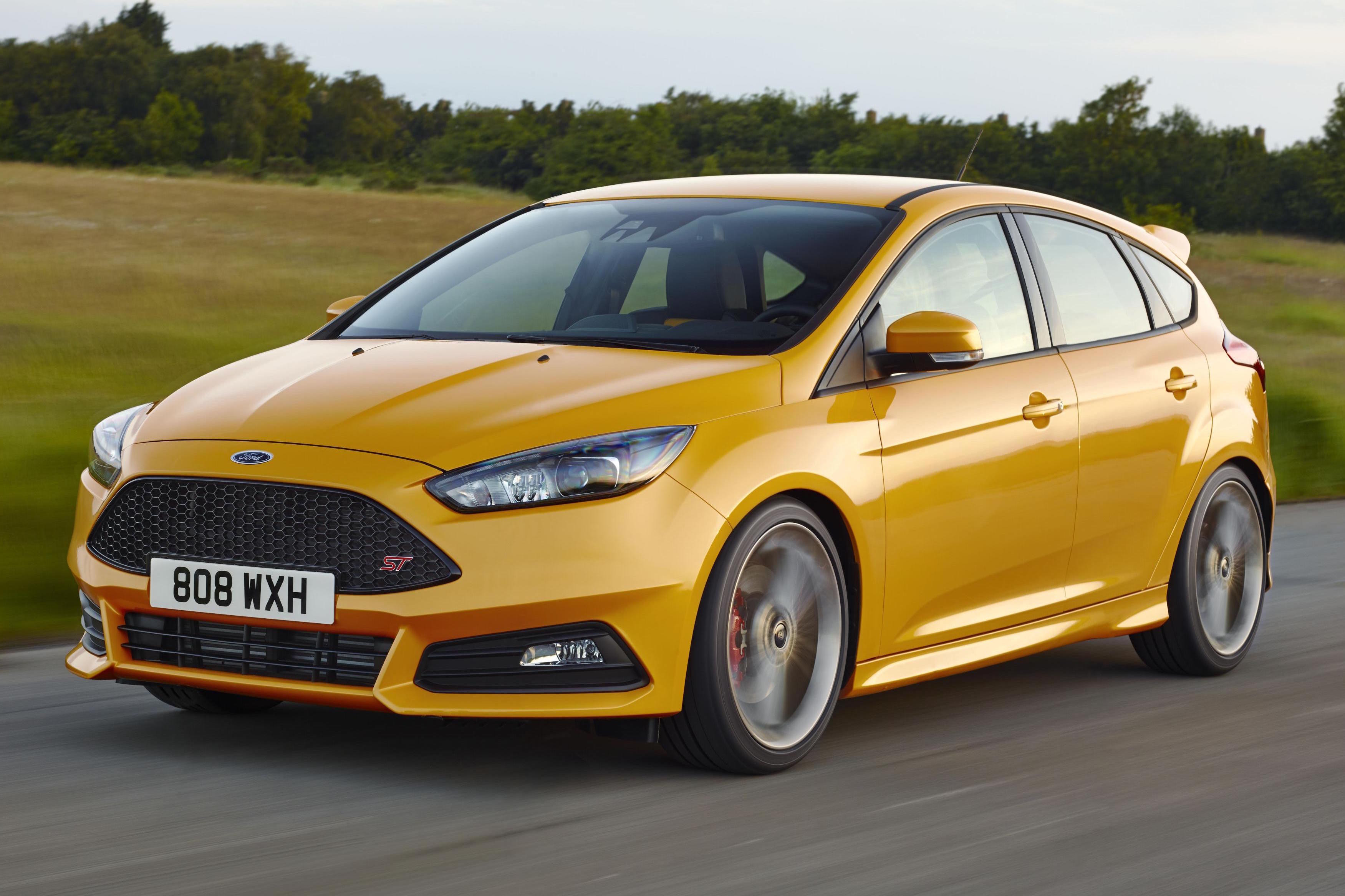 Yellow Ford Fiesta ST driving towards the left on a flat country road