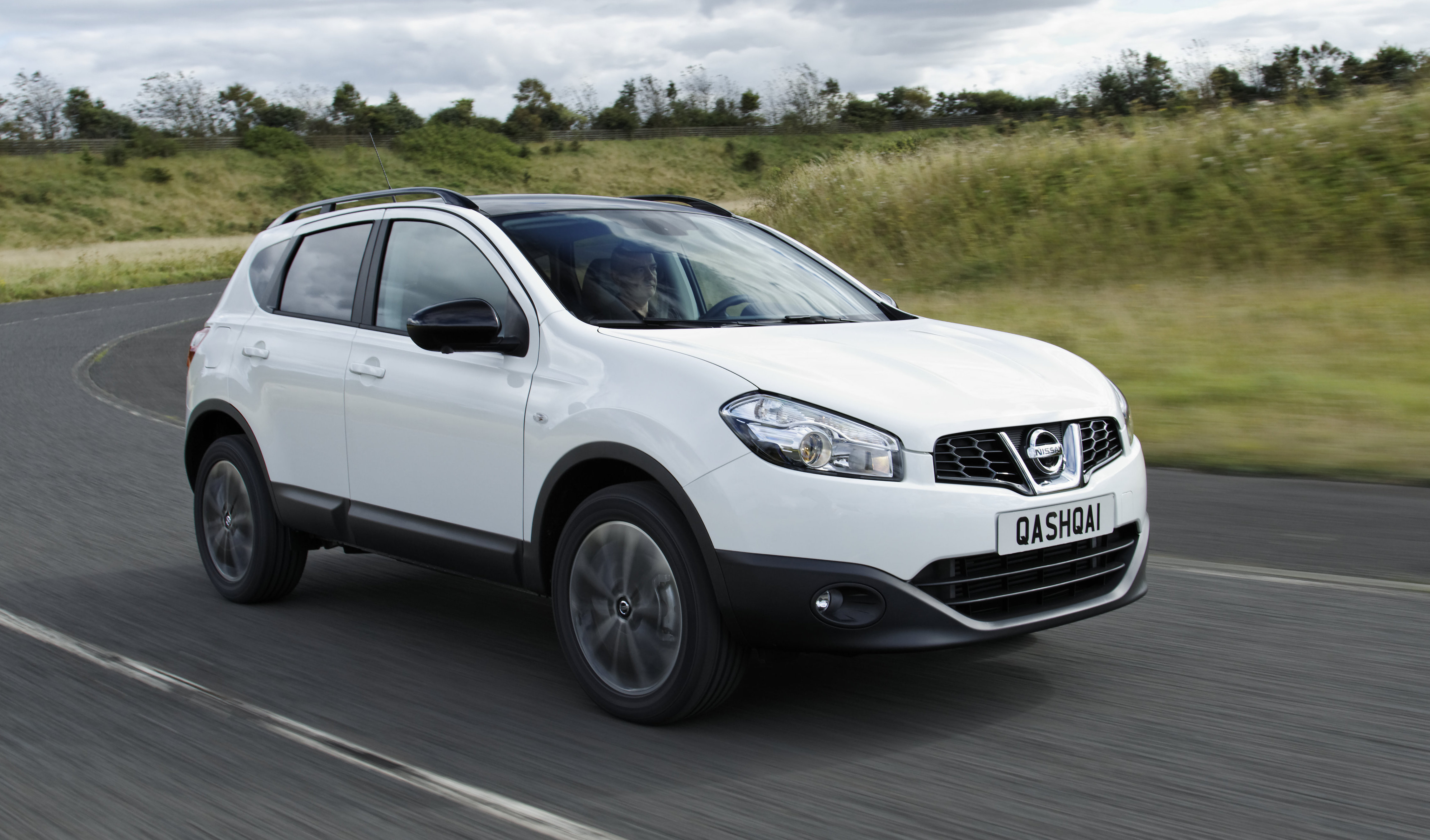 White Nissan Qashqai driving towards the right through countryside