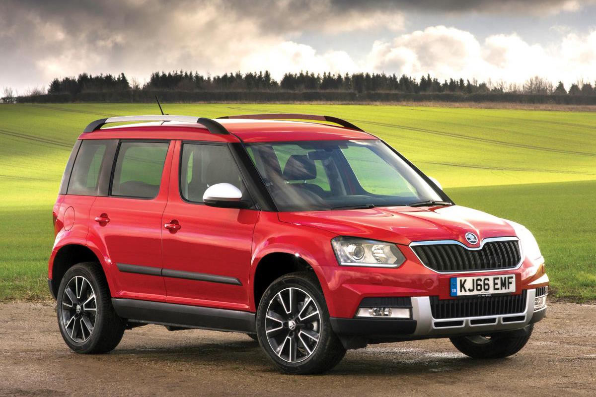 Red ŠKODA Yeti parked facing right in front of a field with tree line in distance