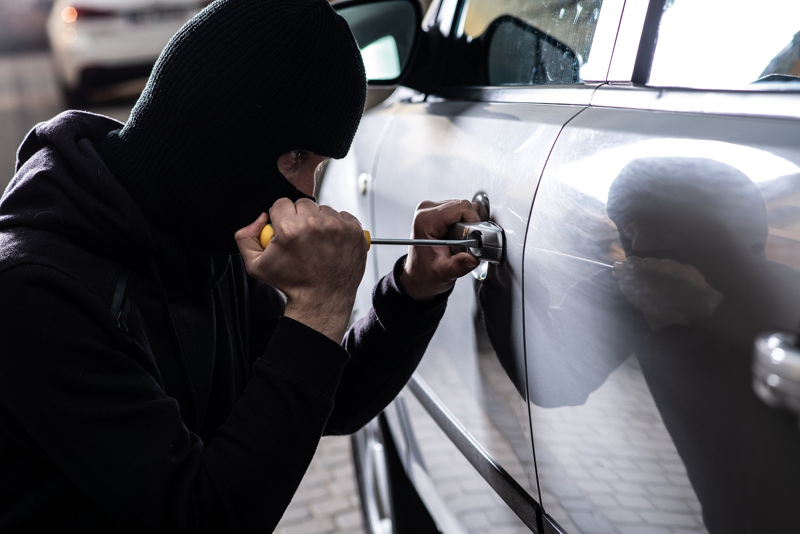 Man in balaclava using screwdriver on car door handle.