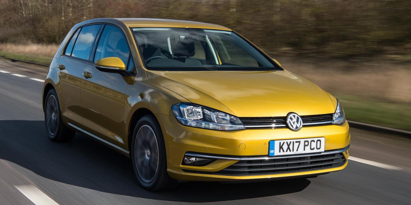 Gold VW Golf travelling towards the right on a tree-lined road