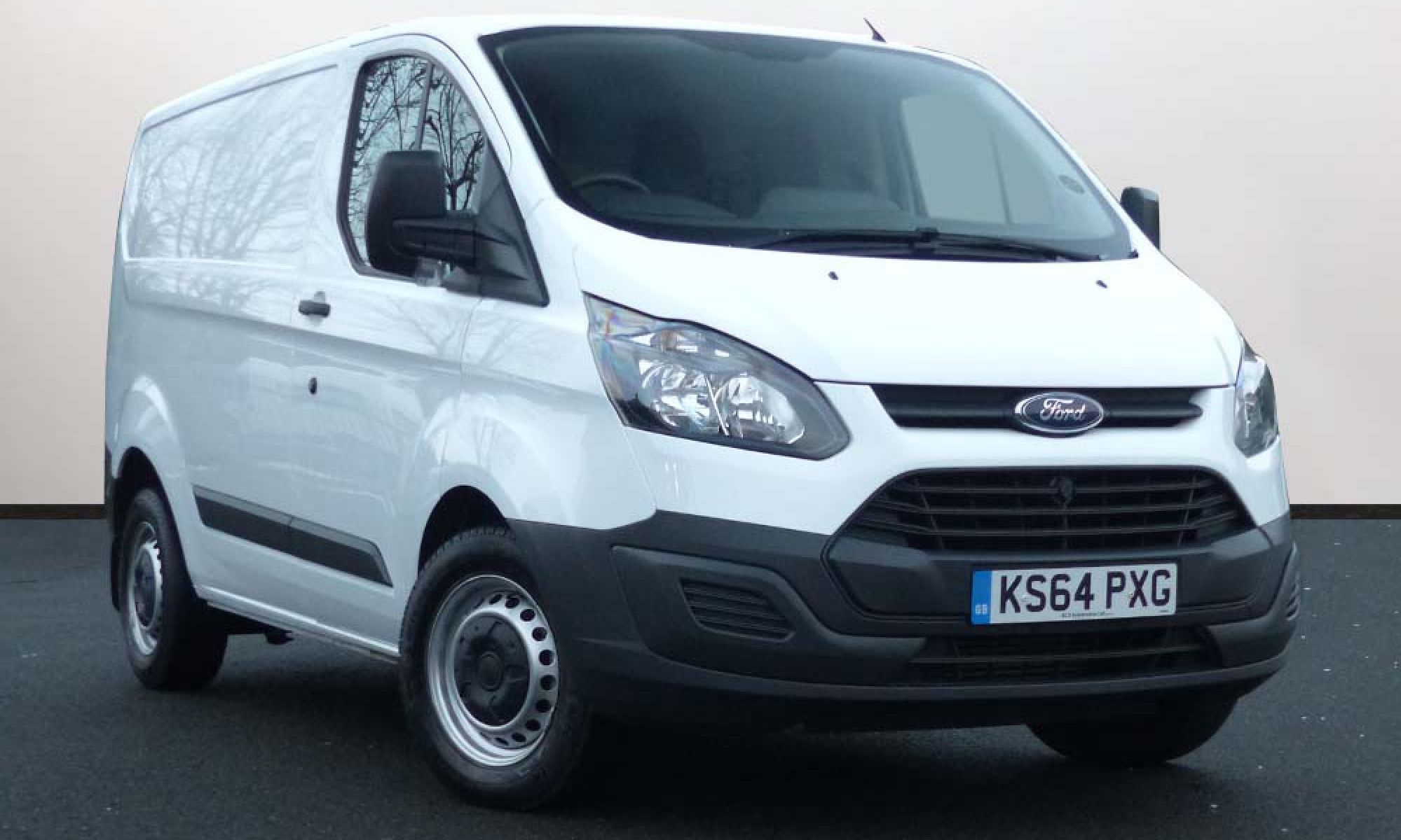 White Ford Transit Custom van parked three-quarters towards right  in front  of white wall