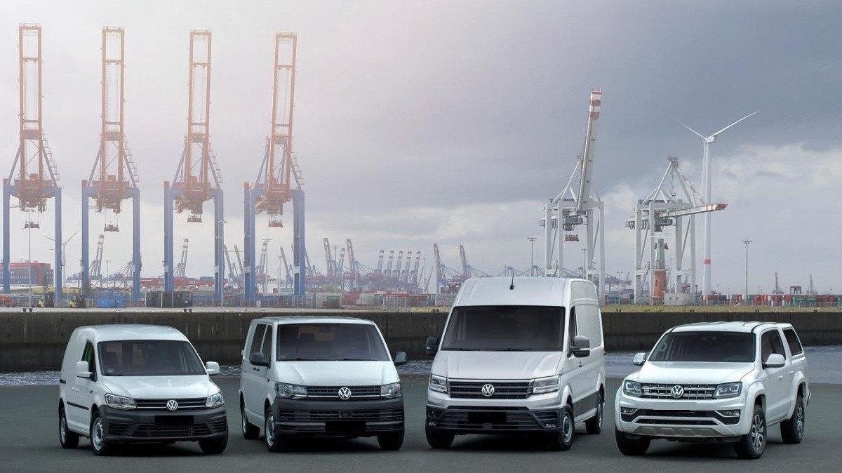 Range of four white Volkswagen vans parked on shipping dockside with four cranes in background.